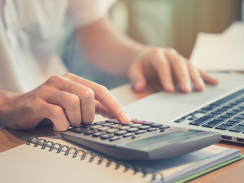 person at desk using calculator