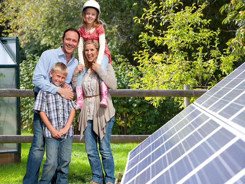 happy family standing next to solar panels
