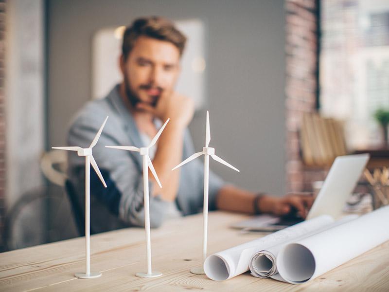 man looking at model wind turbines