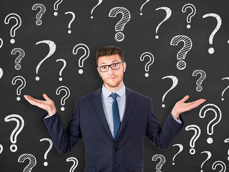 man standing in front of question marks