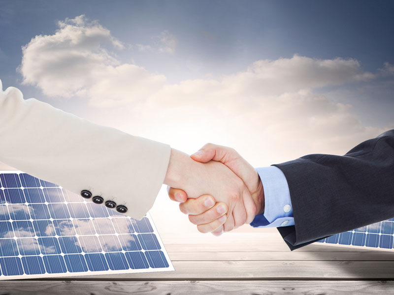 shaking hands over solar panels