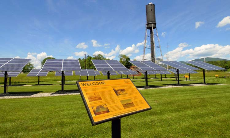 ground-mounted solar panels in a field with a welcome sign