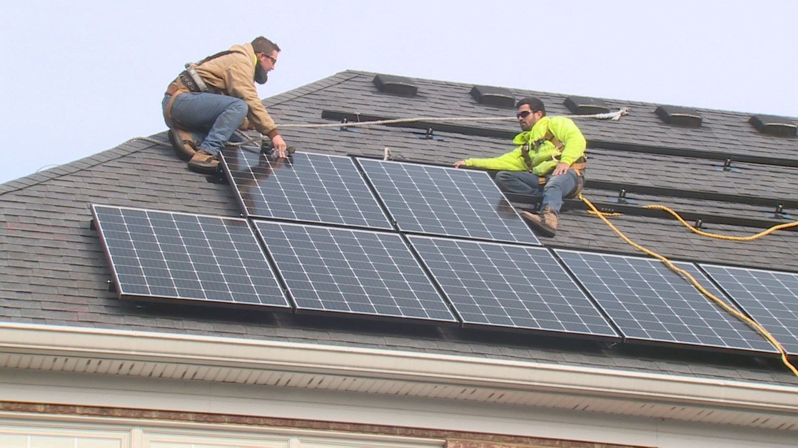two tradesmen install solar panels on a shingled rooftop