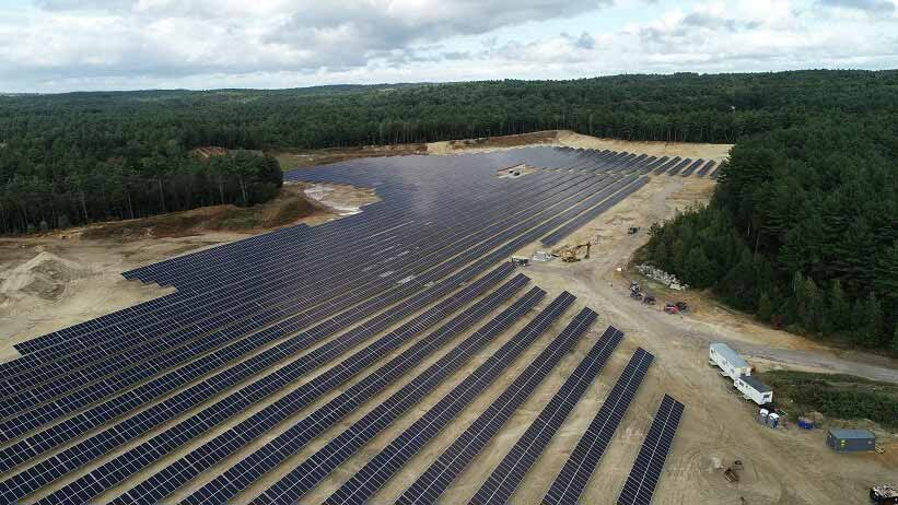 A solar farm surrounded by woods