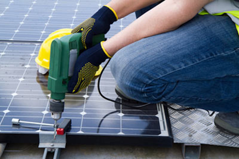 Installing solar panels. Courtesy SolarReviews