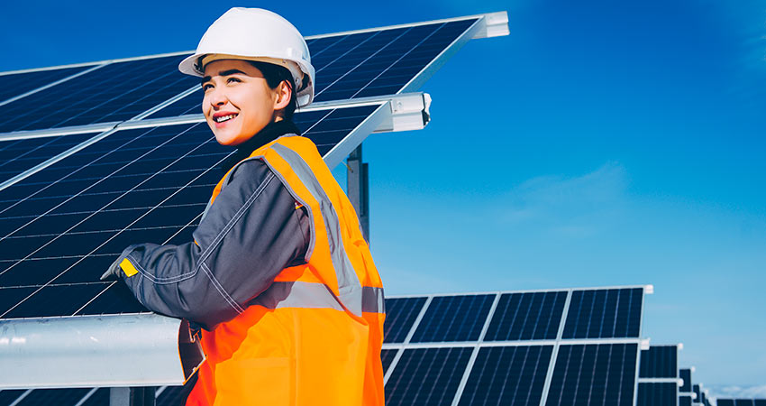 Technician standing in front of solar panels